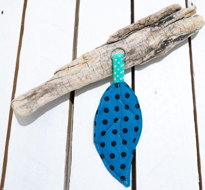 Svjetloplavi privjesak za ključeve u obliku lista uz drvenu pozadinu