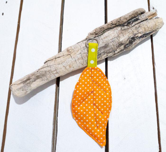 Narančasti privjesak za ključeve u obliku lista uz drvenu pozadinu