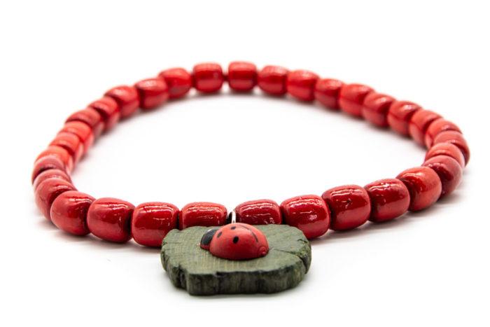 Drvena ogrlica crvene boje s bubamarom na bijeloj pozadini