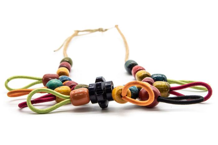 Ogrlica od drvenih kuglica i šarenih vezica na bijeloj podlozi