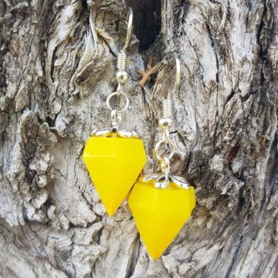 Žute naušnice dijamantnog oblika od epoksi smole na drvenoj kori