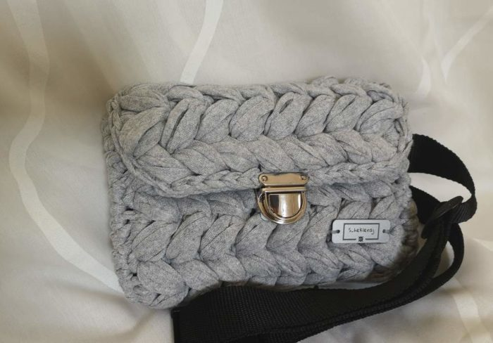 Siva heklana pojasna torbica sa zlatnom kopčom i crnim pojasom na bijeloj pozadini