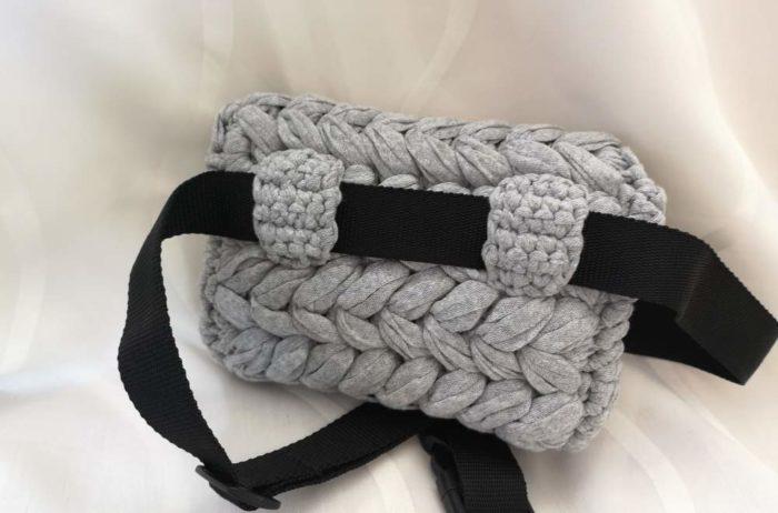 Heklana pojasna torbica straga s crnim pojasom na bijeloj pozadini