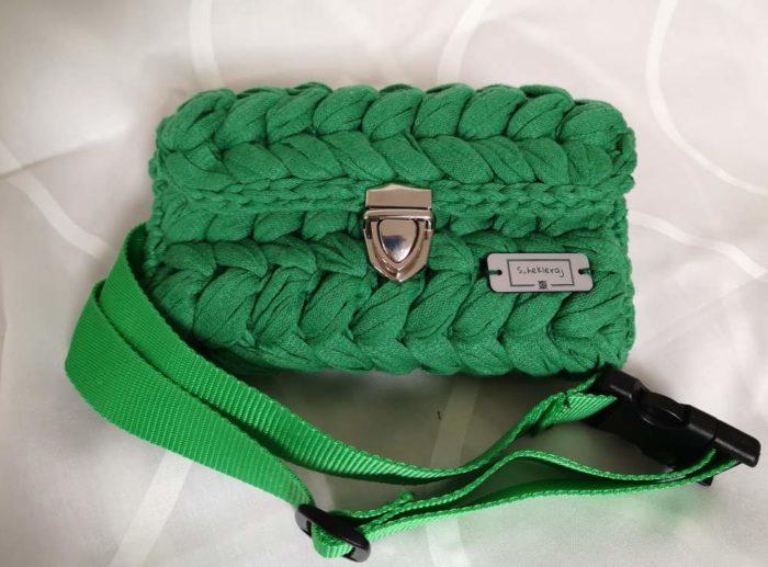 Zelena heklana torbica sa zlatnom kopčom i zelenim pojasom na bijeloj pozadini