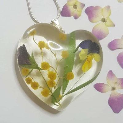 Privjesak od epoksi smole u obliku srca ispunjen sljezom, maćuhicom i mimozom