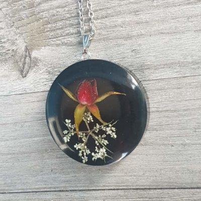 Ogrlica s privjeskom od epoksi smole crne boje sa cvijetom ruže i divlje mrkve na drvenoj podlozi
