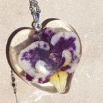Privjesak ogrlice od epoksi smole s cvijetom ljubičaste orhideje na mramornoj podlozi