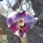Srcoliki privjesak ogrlice od epoksi smole s ljubičastim cvijetom orhideje - visi na stablu