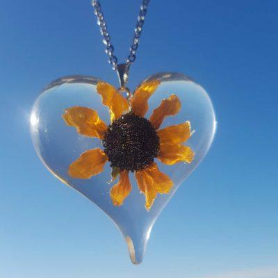 Srcoliki privjesak od epoksi smole sa cvijetom suncokreta na oglici od nehrđajućeg čelika na nebeskoj pozadini