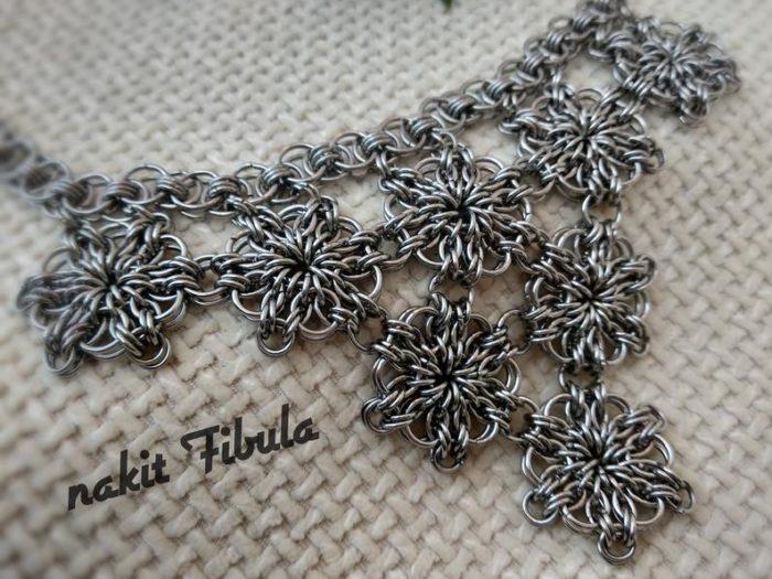 Ogrlica od nehrđajućeg čelika s cvjetnim uzorkom by Nakit Fibula na dekorativnoj pozadini, približena