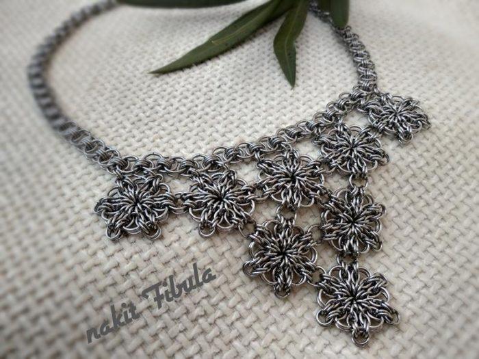 Ogrlica od nehrđajućeg čelika s cvjetnim uzorkom by Nakit Fibula na dekorativnoj pozadini