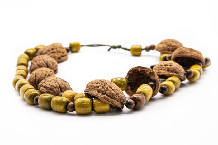 Ogrlica od ljuske oraha i drvenih kuglica na bijeloj podlozi