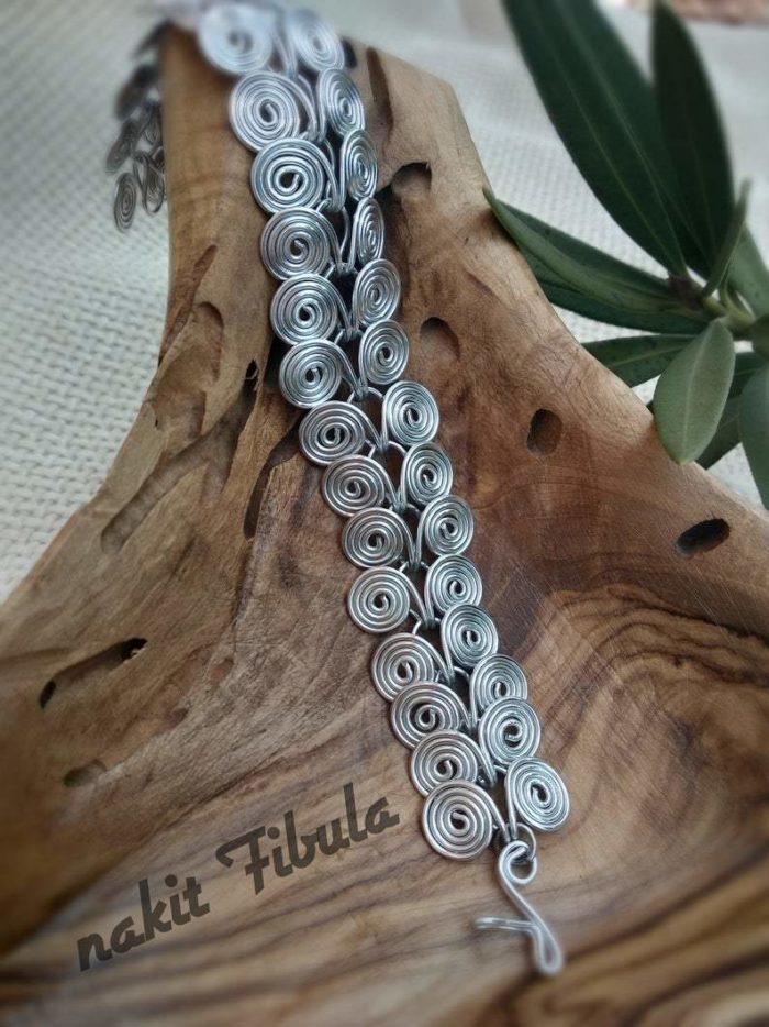 Starorimska spiralna narukvica od aluminija by Nakit Fibula na dekorativnoj drvenoj pozadini (raširena)