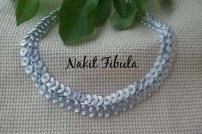Starorimska spiralna ogrlica by Nakit Fibula na dekorativnoj pozadini
