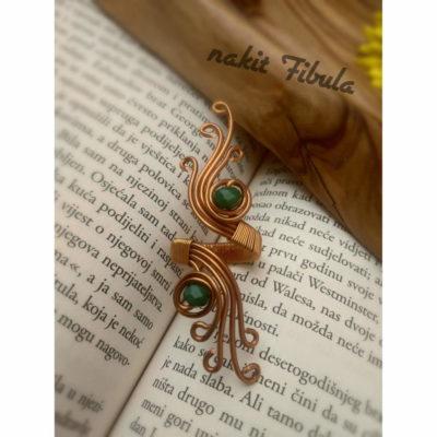 Bakreni prsten by Nakit Fibula izrađen u starorimskoj stilu na knjizi kao dekorativnoj pozadini